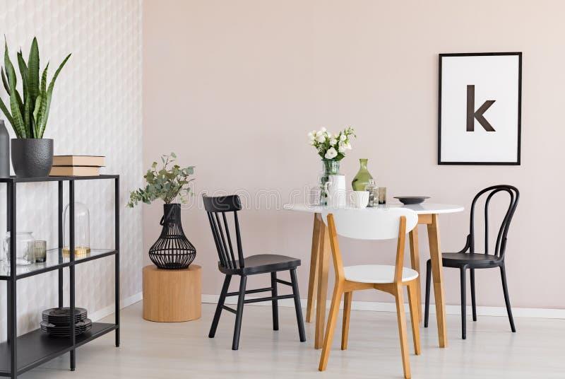 Cadeiras na tabela de madeira com as flores na sala de jantar interior com plantas e cartaz Foto real ilustração royalty free