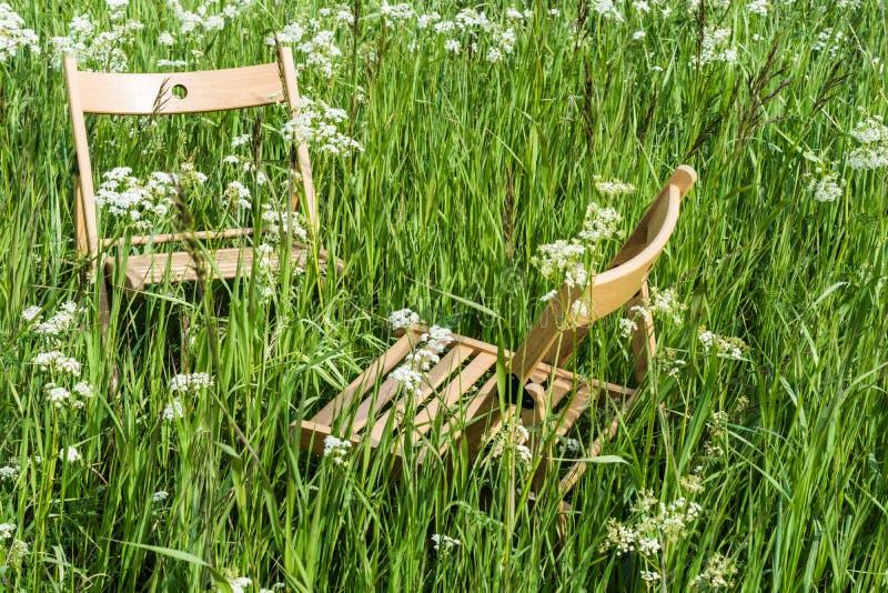 Cadeiras para o abrandamento em um prado verde foto de stock