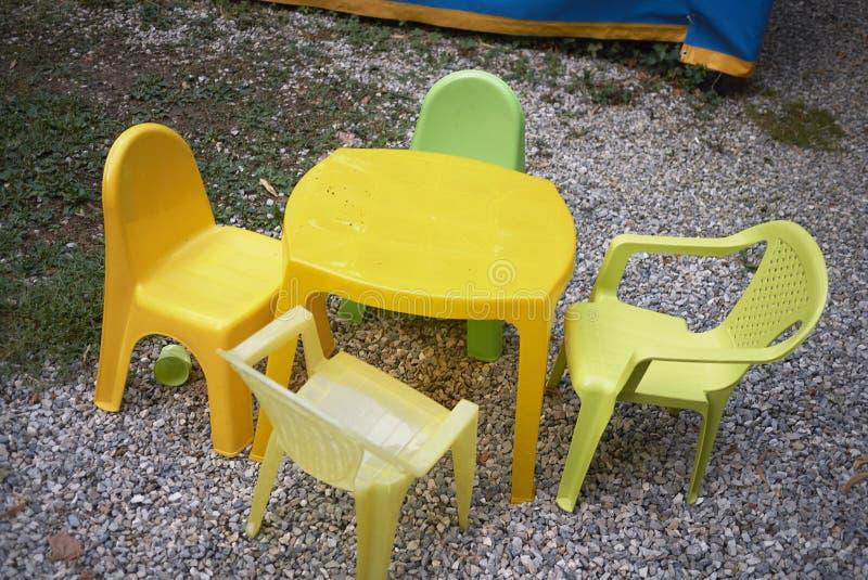 Cadeiras plásticas amarelas em um jardim fotos de stock royalty free