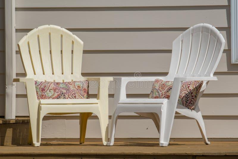Cadeiras plásticas do adirondack do curveback em uma plataforma de madeira do pátio imagens de stock royalty free