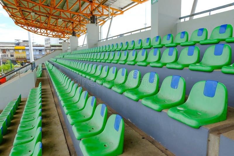 Cadeiras plásticas do verde do estádio do esporte em seguido fotografia de stock