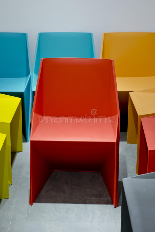 Cadeiras plásticas por cores vermelhas, azuis, alaranjadas imagens de stock
