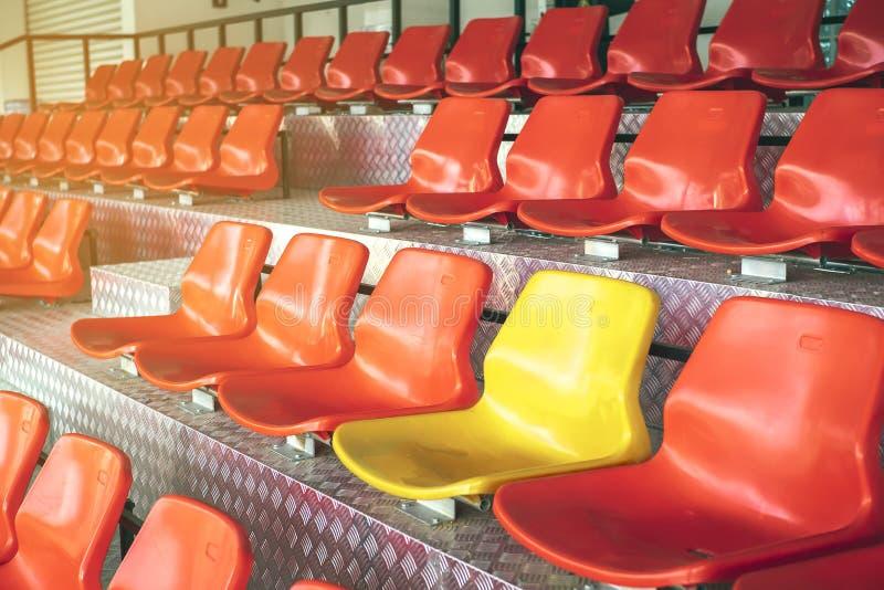 Cadeiras plásticas vermelhas com assentos amarelos no meio Conceito o c fotografia de stock