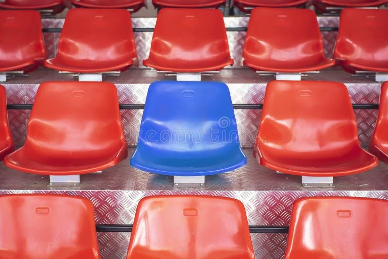 Cadeiras plásticas vermelhas com assentos azuis no meio Conceito o cou imagens de stock