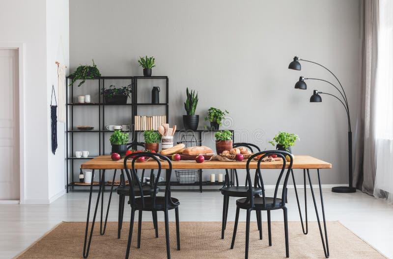 Cadeiras pretas e tabela de madeira com alimento no tapete marrom no interior cinzento da sala de jantar fotografia de stock