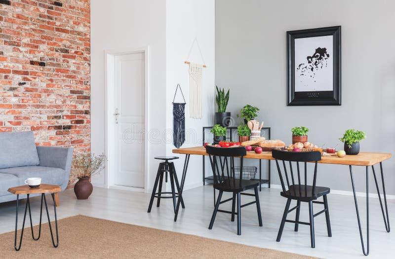 Cadeiras pretas na mesa de jantar e no cartaz no interior liso com o sofá cinzento contra a parede de tijolo vermelho foto de stock
