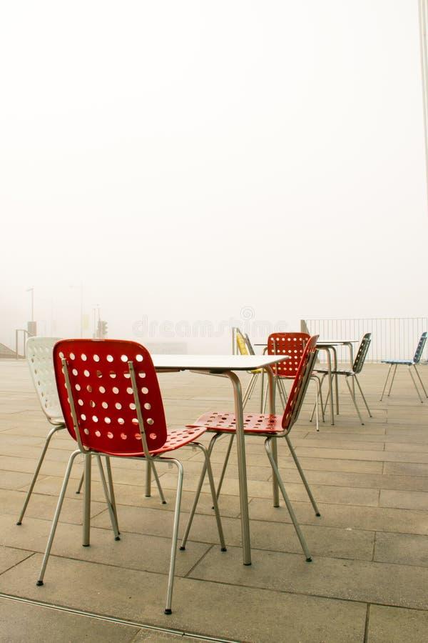 Cadeiras vazias do café na névoa grossa no passeio do beira-mar no outono fotos de stock