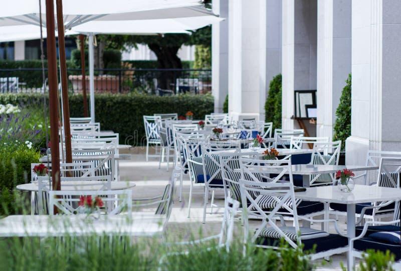 Cadeiras vazias em café ou restaurante ao ar livre no dia de verão imagens de stock royalty free