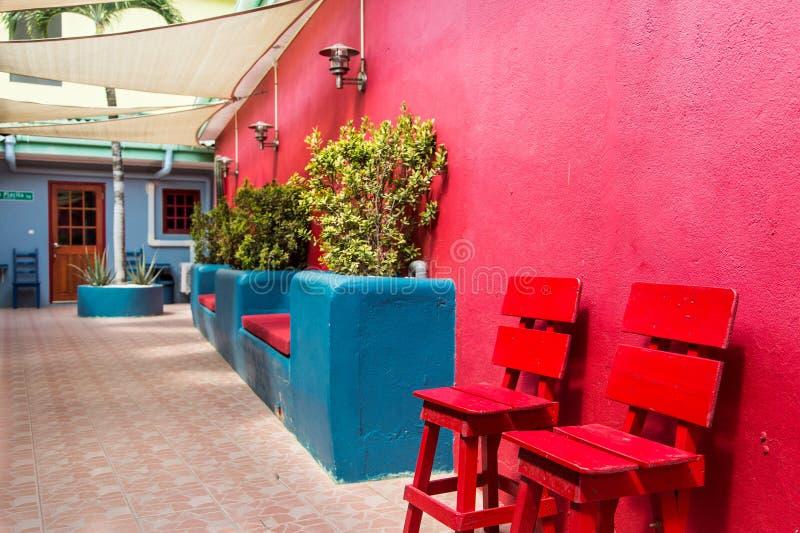 Cadeiras vermelhas e plantador azul fotos de stock royalty free