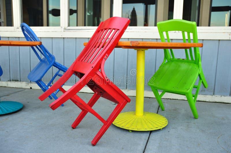 Cadeiras vermelhas, verdes, e azuis que inclinam-se em tabelas