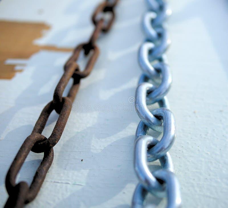 Cadena aherrumbrada vieja al lado de la nueva cadena brillante foto de archivo libre de regalías