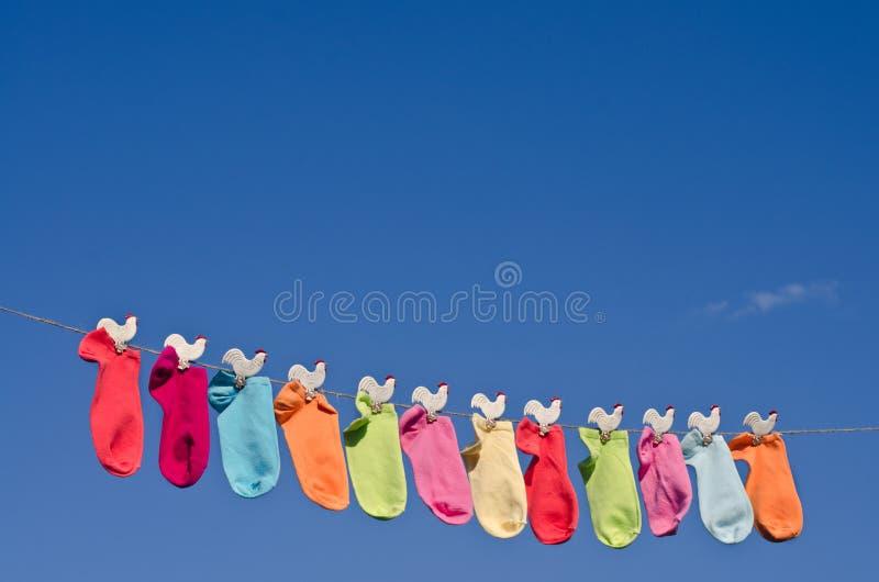 Cadena de calcetines coloridos contra el cielo azul fotos de archivo libres de regalías