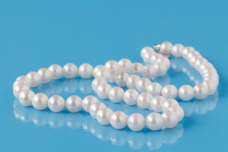 Cadena de perlas en un fondo azul fotos de archivo