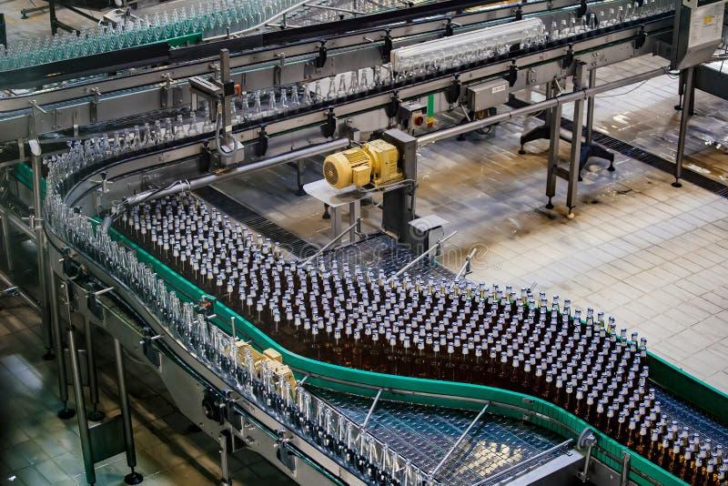 Cadena de producci?n embotelladoa automatizada moderna de la cerveza Botellas de cerveza que mueven encendido el transportador fotografía de archivo libre de regalías