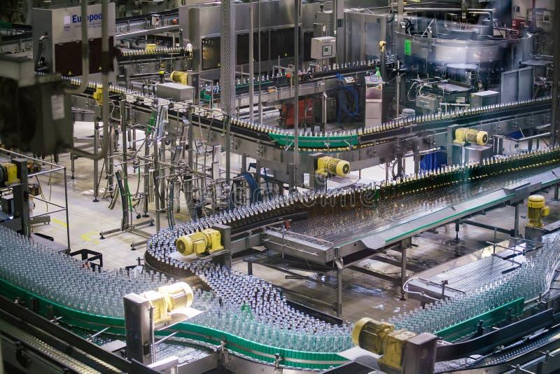 Cadena de producci?n embotelladoa automatizada moderna de la cerveza Botellas de cerveza que mueven encendido el transportador foto de archivo libre de regalías