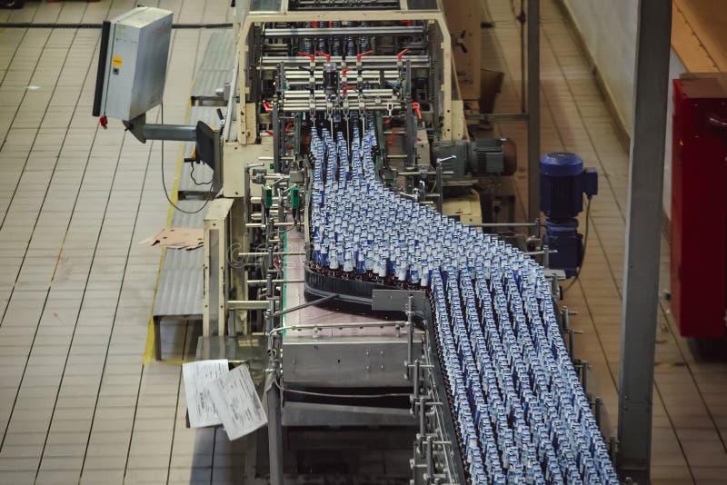 Cadena de producci?n embotelladoa automatizada moderna de la cerveza Botellas de cerveza que mueven encendido el transportador imagen de archivo