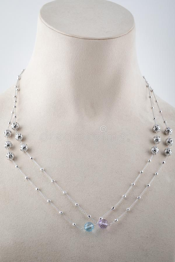 Cadena doble de plata para mujer con dos piedras, púrpura y azul claro en el maniquí blanco foto de archivo