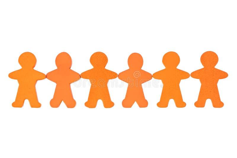 Cadena humana cosechada de figuras de madera anaranjadas contra el fondo blanco imagenes de archivo