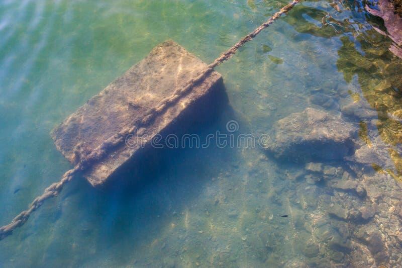 Cadena oxidada debajo del agua, ancla amarre en la orilla imagenes de archivo
