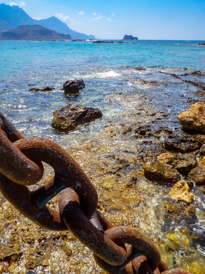 Cadena oxidada grande de la nave, agua azul baja y costa costa rocosa fotos de archivo