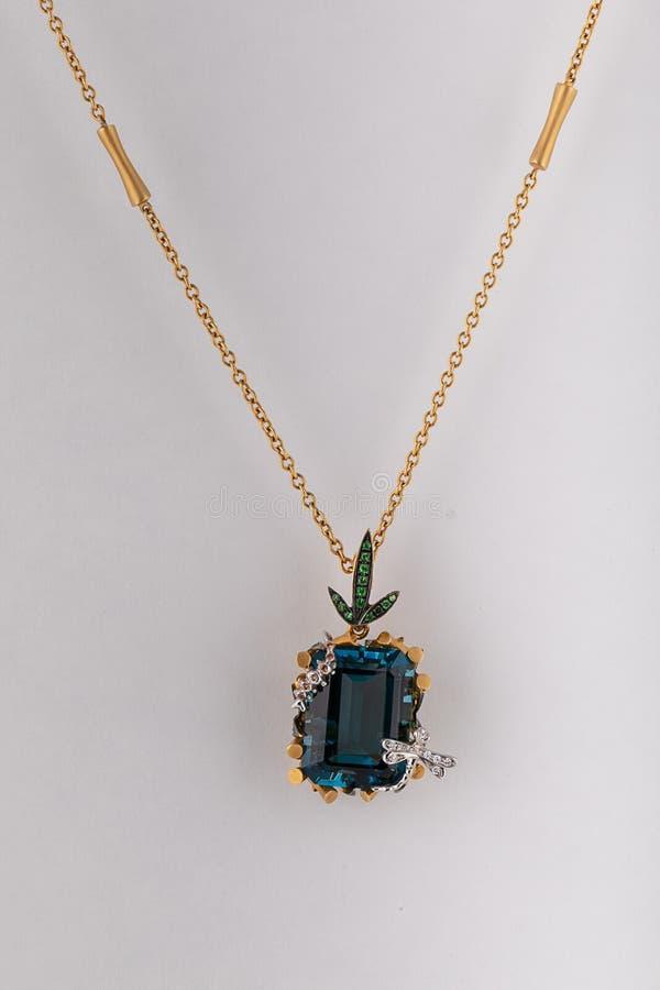 Cadena para mujer del oro con un colgante de la piedra azul en la forma de un rectángulo con una libélula de plata aislada en un  imagenes de archivo