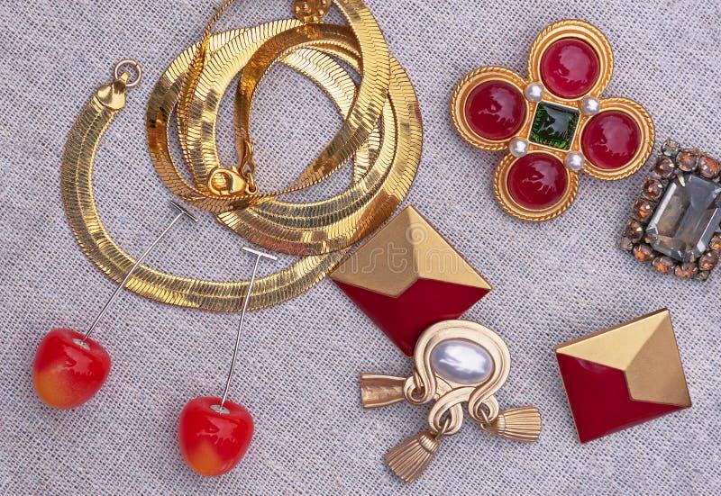 Cadena, pendientes, broche en rojo y diseño del oro Bijouterie Fondo de la joyería para el diseño y la decoración imagen de archivo