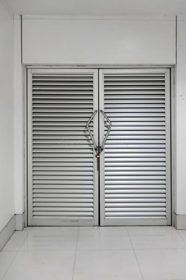 Cadena y cerradura en la manija del metal de la puerta de aluminio imagen de archivo