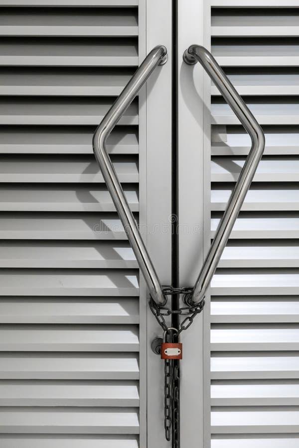 Cadena y cerradura en la manija del metal de la puerta de aluminio fotos de archivo