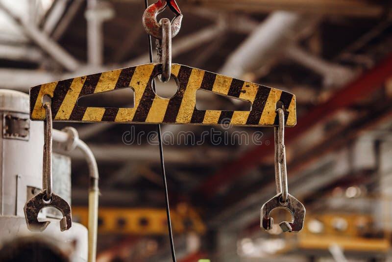 Cadena y gancho de la grúa con el fondo borroso del almacén Fábrica de acero de la producción del concepto imagenes de archivo
