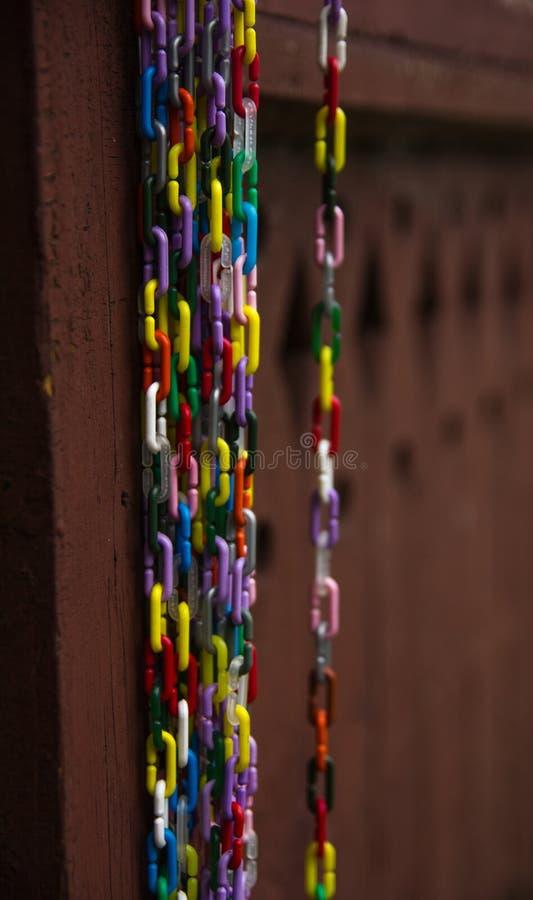 Cadenas coloreadas decorativas en una pared de madera vieja fotografía de archivo