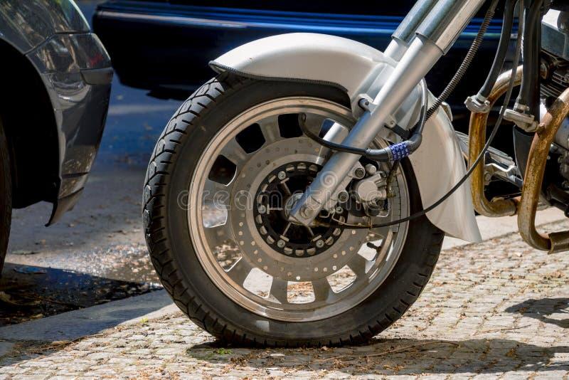 Cadenas de nombre de sécurité bloquant la roue de moto sur la rue image stock