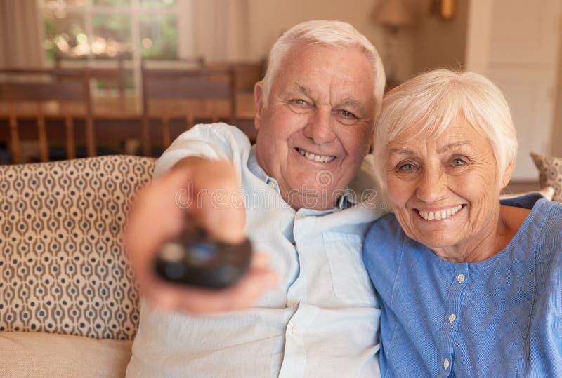 Cadenas de televisión cambiantes sonrientes de los pares mayores con un telecontrol foto de archivo libre de regalías