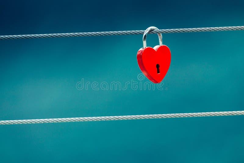 Cadenas rouge de serrure d'amour sur le pont extérieur photographie stock