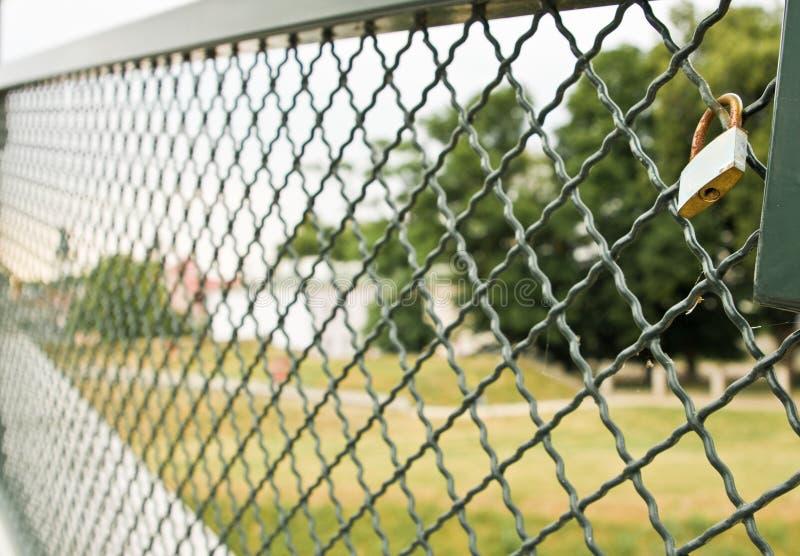 Cadenas simple fixé à une barrière en métal image libre de droits