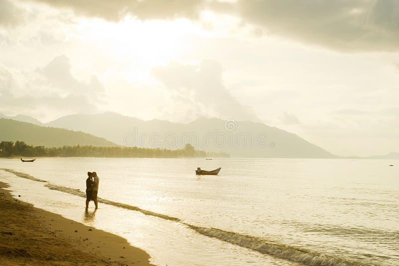 Cadendo nelle coppie di amore sulla spiaggia fotografia stock