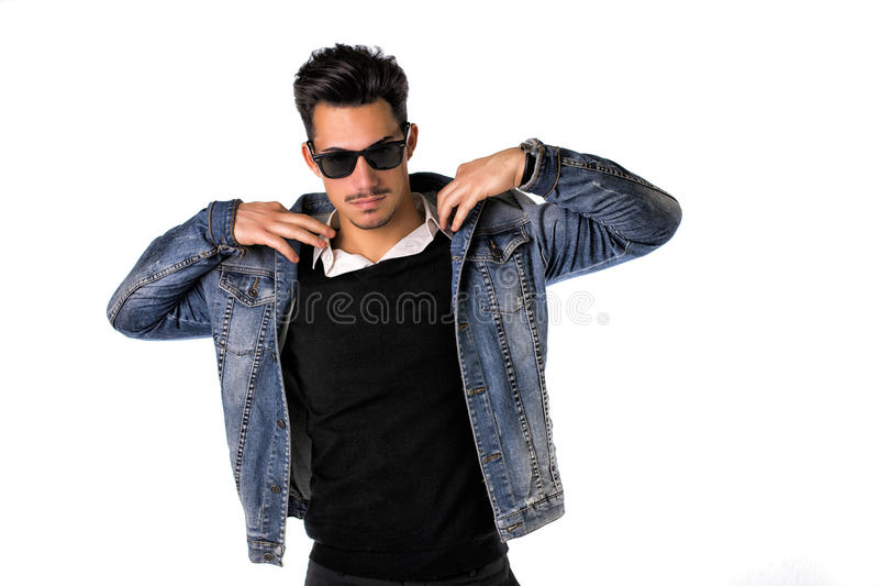 Cadera, hombre joven de moda con las gafas de sol y chaqueta del dril de algodón imagen de archivo