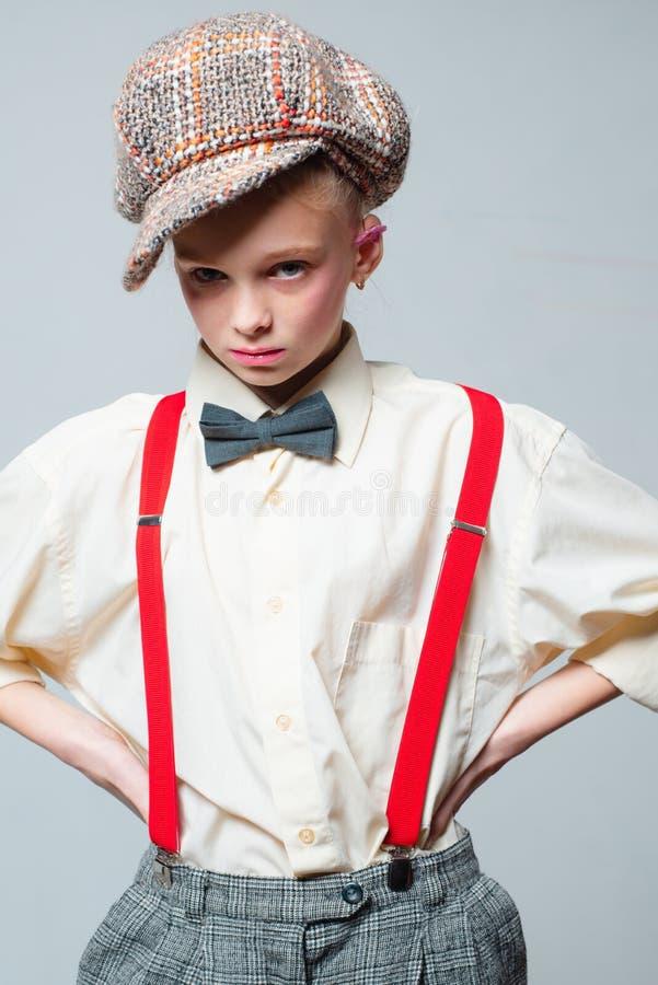Cadera y elegante muchacha adolescente en traje masculino retro estilo ingl?s del vintage moda del paso del jazz Liga y corbata d imagen de archivo libre de regalías
