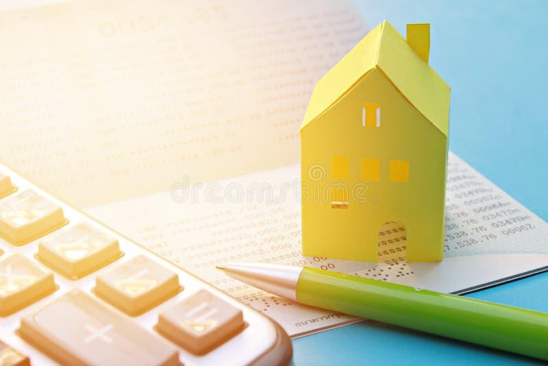 Caderneta bancária de conta poupança, calculadora, pena e casa de papel amarela no fundo azul imagens de stock