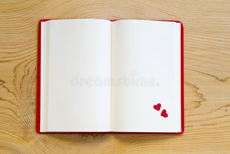 Caderno aberto com coração vermelho no fundo de madeira imagens de stock royalty free