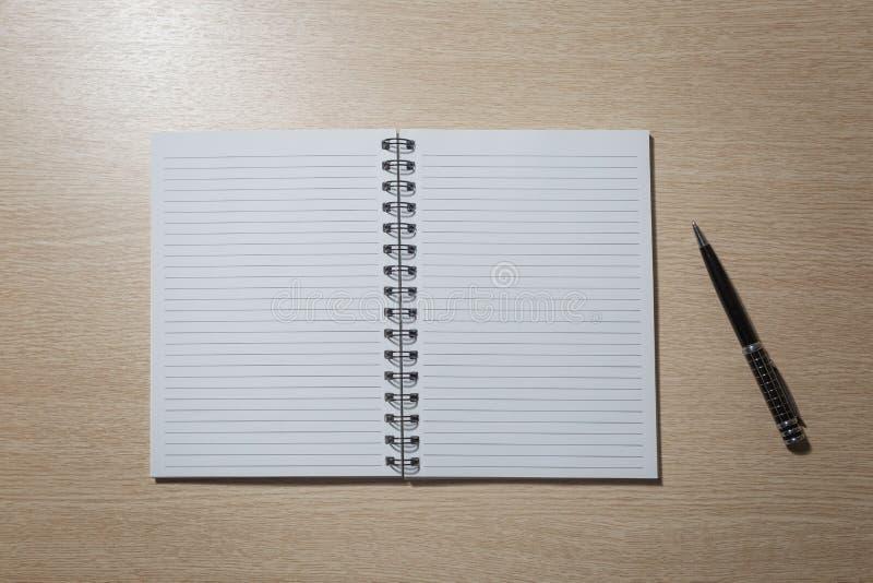 Caderno aberto com uma tira e com uma pena de bola em uma mola em uma tabela de madeira clara fotos de stock
