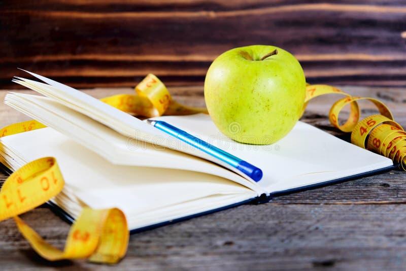 Caderno aberto da placa com a fita verde do centímetro da maçã e do amarelo Esporte do conceito, dieta, aptidão, comer saudável imagens de stock royalty free