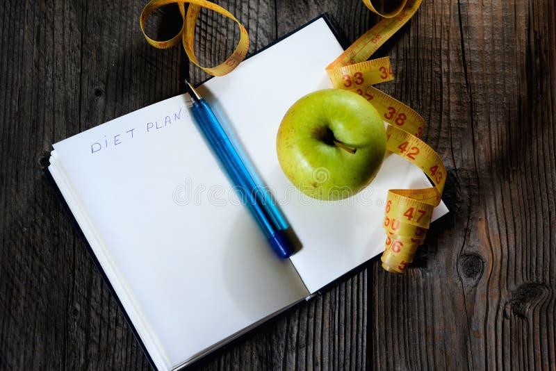 Caderno aberto da placa com a fita verde do centímetro da maçã e do amarelo Esporte do conceito, dieta, aptidão, comer saudável fotos de stock