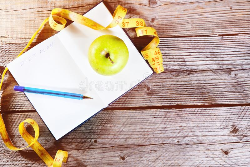 Caderno aberto da placa com a fita verde do centímetro da maçã e do amarelo Esporte do conceito, dieta, aptidão, comer saudável fotografia de stock