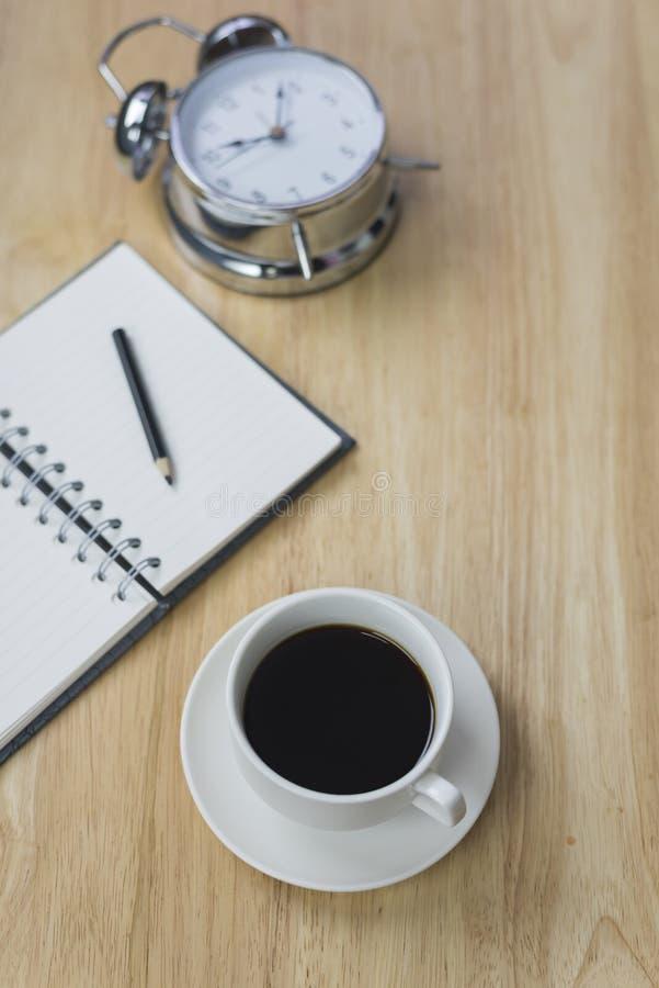 Caderno aberto do café preto com lápis e antiquado obscuros imagem de stock royalty free