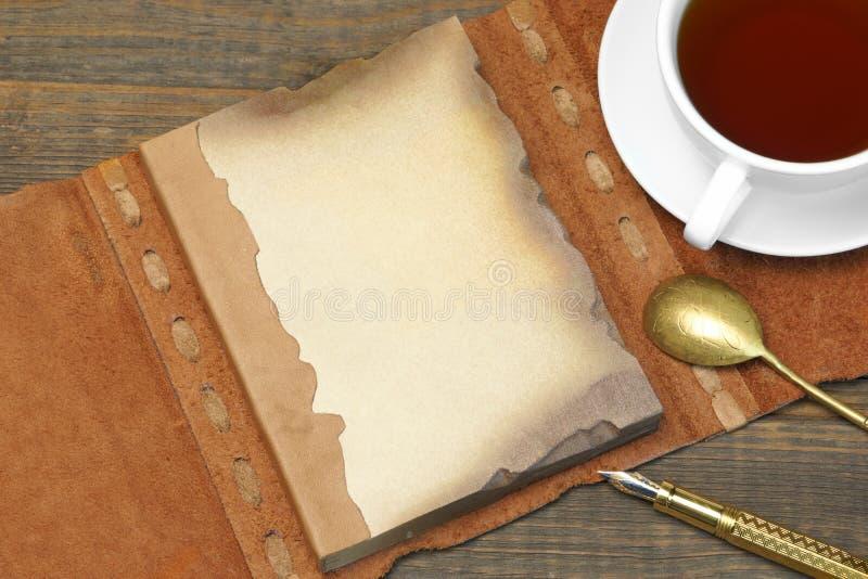 Caderno aberto do vintage com a página vazia de Brown, pena, xícara de chá, Spoo foto de stock royalty free