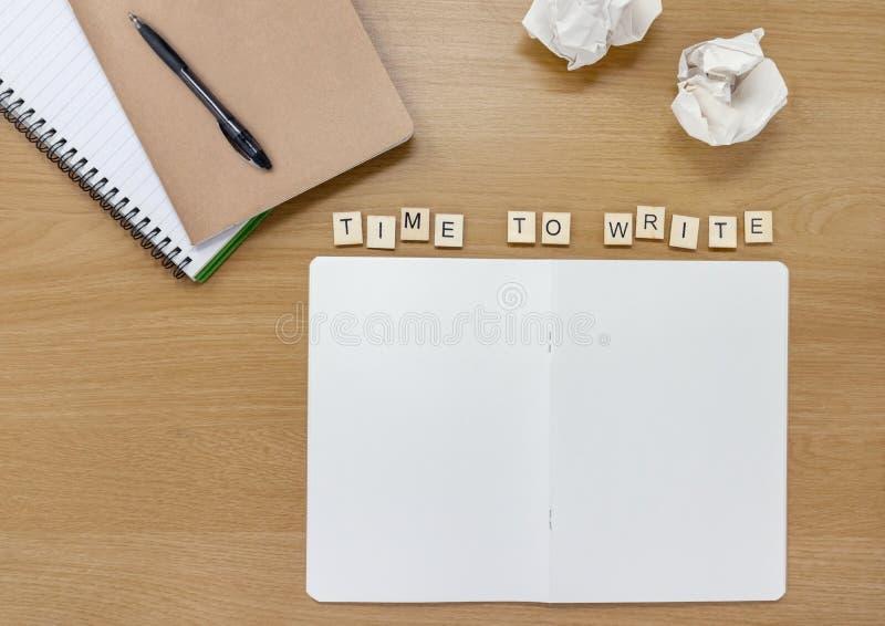 Caderno aberto em um escritor ou em uma mesa dos artistas, com as telhas que soletram para fora 'a hora de escrever ' imagens de stock royalty free