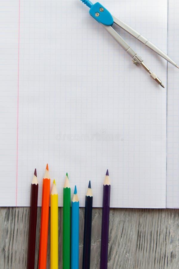 caderno aberto em uma configuração de madeira da tabela ao lado dos lápis e dos compassos coloridos imagens de stock royalty free