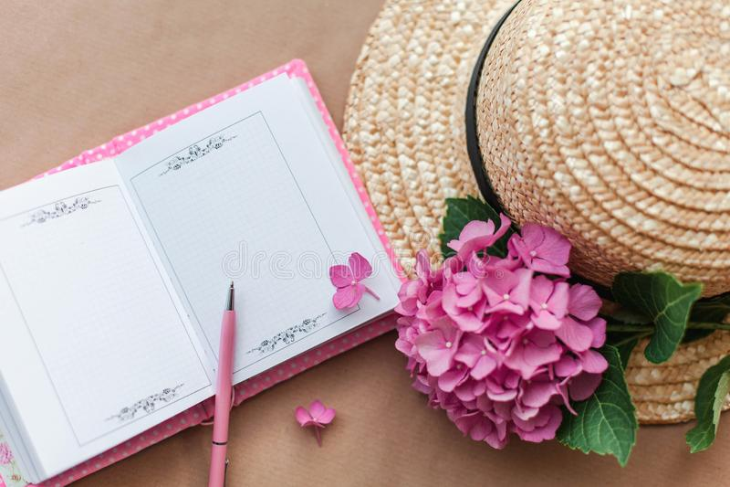 Caderno aberto fêmea com pena, as flores da hortênsia e o chapéu de palha cor-de-rosa Local de trabalho romântico para sonhar imagem de stock royalty free