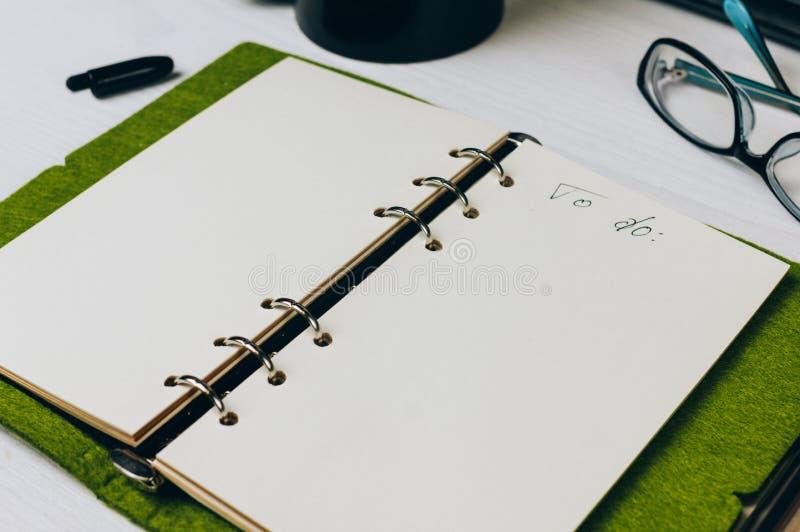 Caderno aberto na tabela da cor branca imagens de stock royalty free