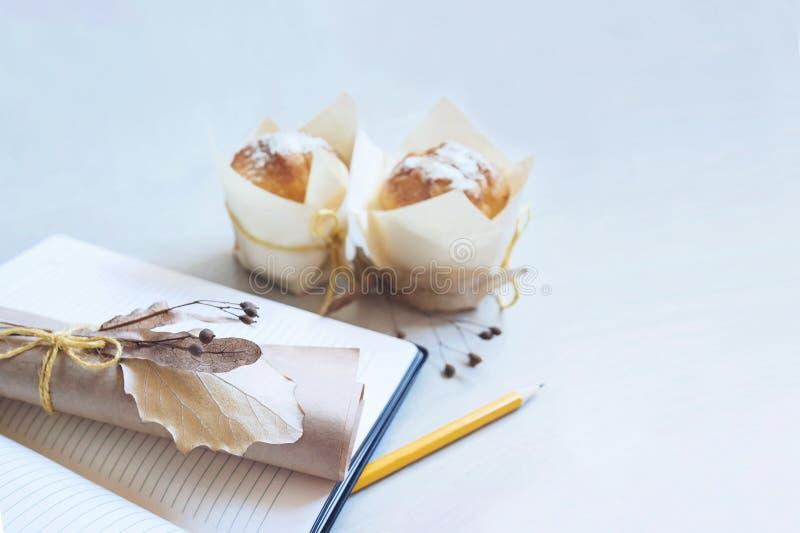 Caderno branco da placa da tabela da mesa com o lápis e o papel vazio dobrado, decorados com flores secadas Vista superior com sp fotos de stock